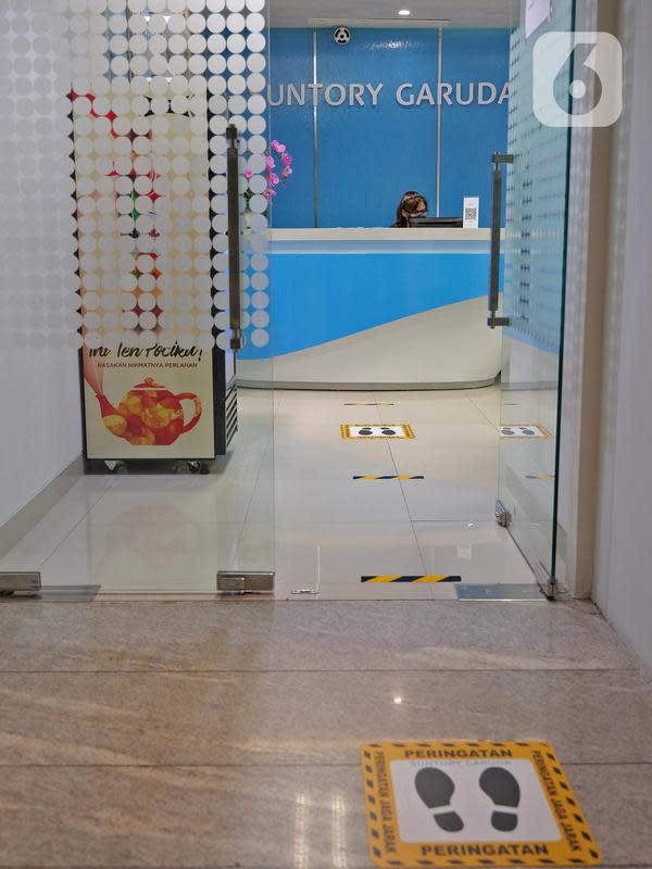 Tanda jaga jarak yang dipasang di lantai kantor Suntory Garuda, Jakarta, Senin (8/8/2020). Suntory Garuda menerapkan protokol kesehatan, seperti kapasitas karyawan hanya dibolehkan sebanyak 50 persen, meniadakan absensi sidik jari dan menggunakan alat makan pribadi. (Liputan6.com/Herman Zakharia)