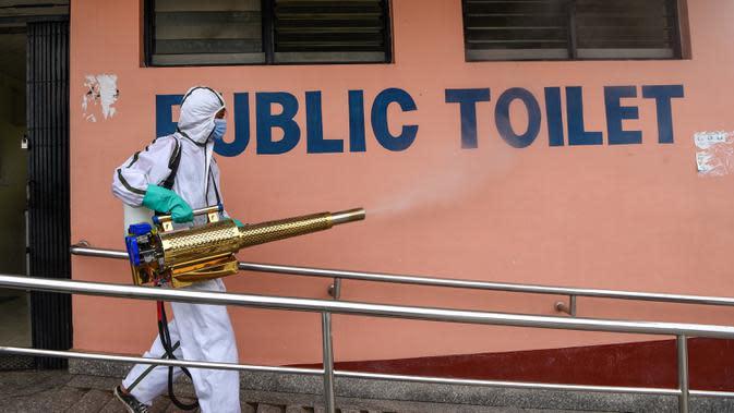 Pekerja yang mengenakan Alat Pelindung Diri (APD) menyemprotkan disinfektan toilet umum di terminal bus di Kathmandu, Kamis (17/9/2020). Pemerintah Nepal melonggarkan pembatasan yang diberlakukan sebagai tindakan pencegahan virus corona pada transportasi umum jarak jauh. (PRAKASH MATHEMA/AFP)