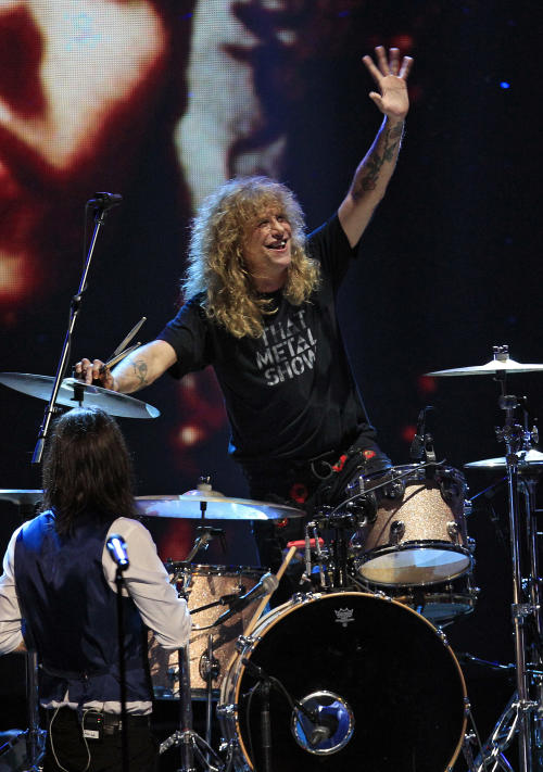 Guns N' Roses drummer Steven Adler waves during a performance after the band's induction into the Rock and Roll Hall of Fame early Sunday, April 15, 2012, in Cleveland. (AP Photo/Tony Dejak)
