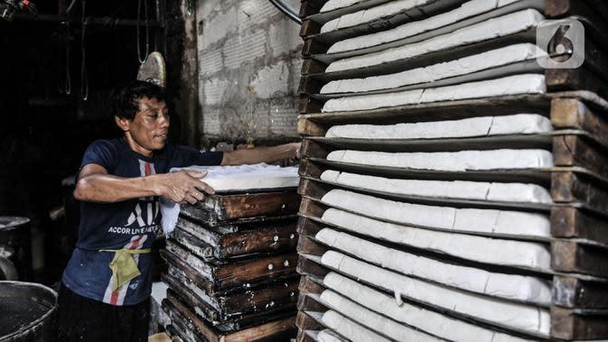 Pekerja saat menyelesaikan pembuatan tahu di salah satu industri rumahan kawasan Mampang, Jakarta, Minggu (30/8/2020). Covid-19 menyebabkan produksi tahu di industri rumahan menurun drastis dibandingkan sebelum merebaknya pandemi. (merdeka.com/Iqbal S. Nugroho)