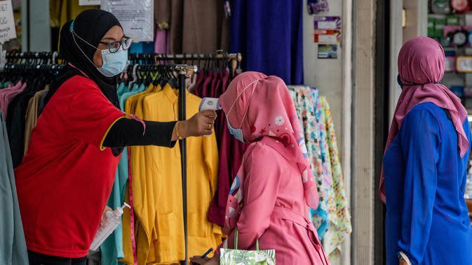 Pekerja memeriksa suhu seorang wanita Muslim, sebagai tindakan pencegahan penyebaran Covid-19 sebelum memasuki toko yang menjual pakaian budaya Malaysia atau baju melayu dan baju kurung menjelang Idul Fitri yang menandai berakhirnya bulan suci Ramadan di Kuala Lumpur (13/5/2020). (AFP/Mohd Rasfan)