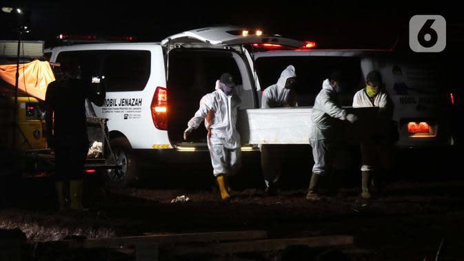 Petugas mengangkat peti jenazah yang akan dimakamkan dengan protokol COVID-19 di TPU Pondok Ranggon, Jakarta, Sabtu (17/10/2020). Pada Sabtu (17/10), 32 jenazah dimakamkan dengan protokol COVID-19 di TPU Pondok Ranggon. (Liputan6.com/Helmi Fithriansyah)