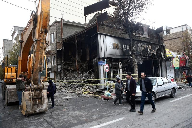 People walk near a burnt bank, after protests against increased fuel prices, in Tehran