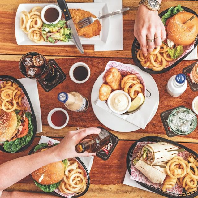 A table full of Hog's Breath meals, including burgers, wraps and their famous curly fries.