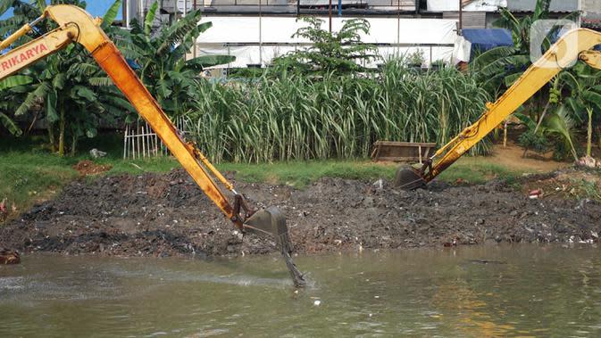 Alat berat mengeruk sampah bercampur lumpur di aliran Banjir Kanal Barat, Jakarta, Rabu (14/10/2020). Pengerukan serta pembersihan waduk, sungai, dan saluran air dari lumpur juga sampah untuk mencegah pendangkalan serta mengantisipasi banjir saat musim hujan. (Liputan6.com/Immanuel Antonius)