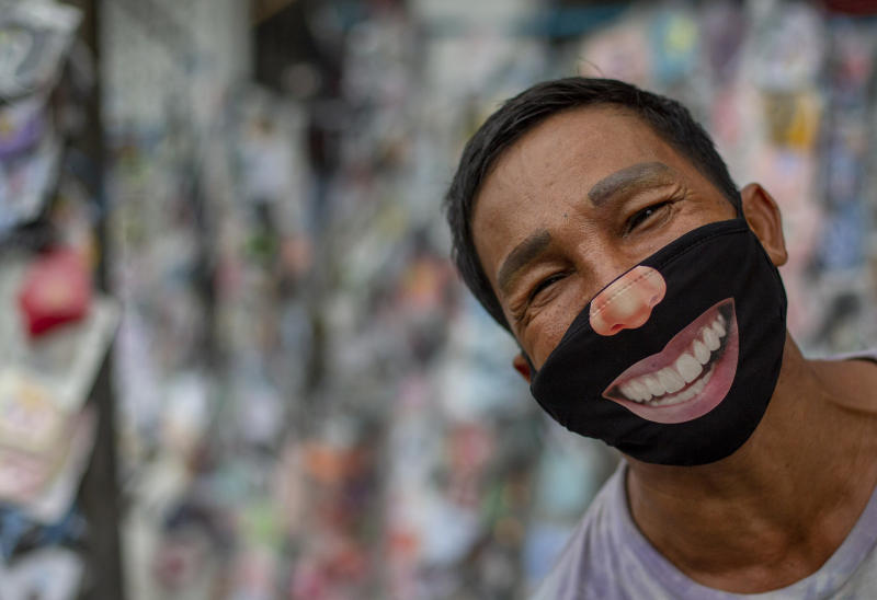 A mask seller wearing a mask stands in a street market in Bangkok, Thailand, Tuesday, June 9, 2020. Daily life in capital resuming to normal as Thai government continues to ease restrictions related to running business in capital Bangkok that were imposed weeks ago to combat the spread of COVID-19. (AP Photo/ Gemunu Amarasinghe)