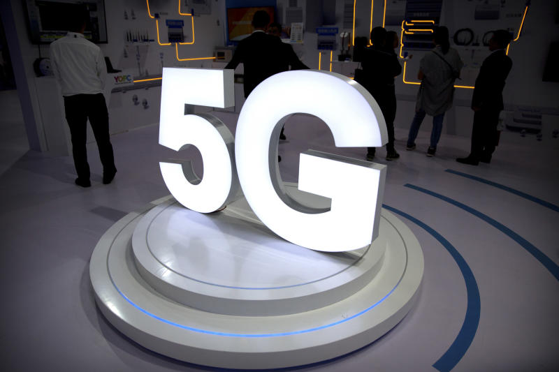 """FILE- In this Sept. 26, 2018, file photo visitors stand near a 5G logo at a display the PT Expo in Beijing. AT&T says it will stop advertising its wireless network as """"5G Evolution"""" after an industry group determined it was misleading, as it is not, in fact, 5G. (AP Photo/Mark Schiefelbein, File)"""