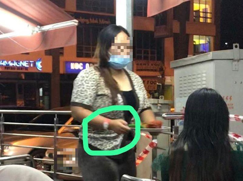 Picture of a woman sporting the pink Person Under Surveillance for Covid-19 wristband and dining out at a restaurant said to be in Ipoh, Perak were shared online today. — Picture from social media