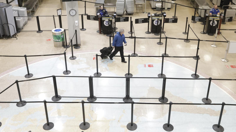 A traveler walks through the security line at the Salt Lake City International Airport Wednesday, March 25, 2020, in Salt Lake City. For the millions of Americans living under some form of lockdown to curb the spread of the new coronavirus, not knowing when the restrictions will end is a major source of anxiety. (AP Photo/Rick Bowmer)