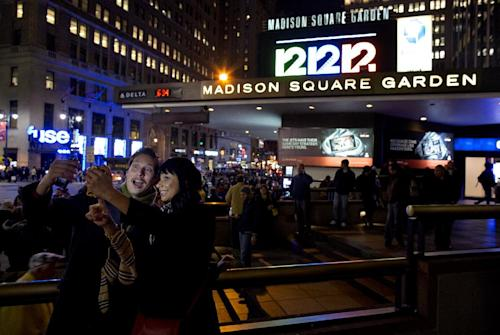"""Friends Steve Ramos, of Los Angeles, and Viviana Barraza, of Bridgeport, Conn., take a photo of themselves before attending the """"12-12-12"""" benefit concert at Madison Square Garden in New York Wednesday, Dec. 12, 2012. Music royalty from the Rolling Stones to Kanye West are gathering at Madison Square Garden for a benefit concert to help storm victims. (AP Photo/Craig Ruttle)"""