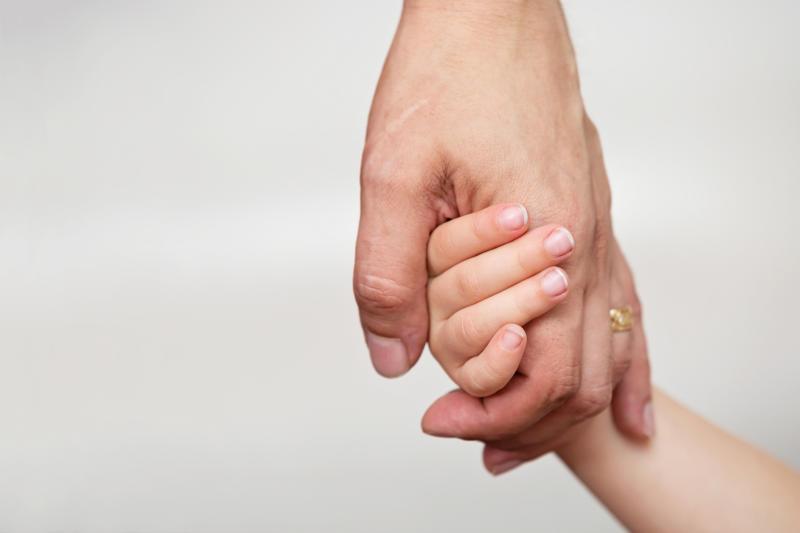 A man holding little girl's hand.