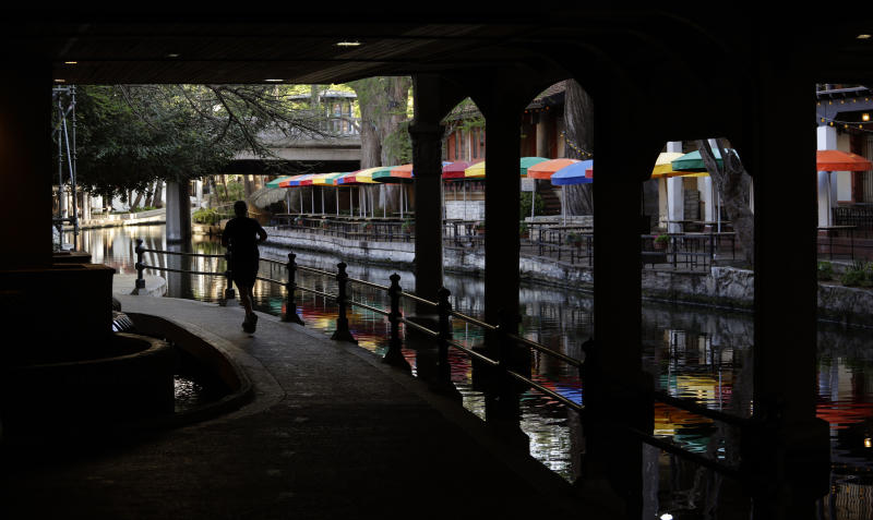 FILE - In this March 24, 2020, file photo, a runner moves along a mostly deserted River Walk in San Antonio, where most restaurants and business are closed. (AP Photo/Eric Gay, File)