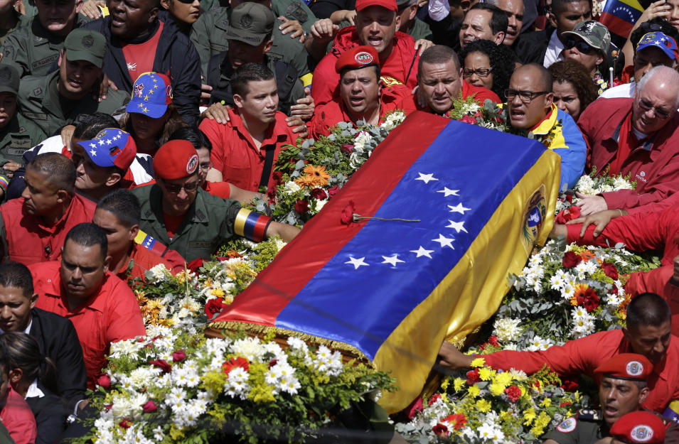 The flag-draped coffin containing the body of Venezuela's late President Hugo Chavez is taken from the hospital where he died, to a military academy where it will remain until his funeral in Caracas, Venezuela, Wednesday, March 6, 2013. Seven days of mourning were declared, all schools were suspended for the week and friendly heads of state were expected for an elaborate funeral Friday. (AP Photo/Ricardo Mazalan)