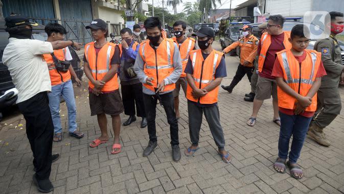 Petugas menghukum warga pelanggar PSBB yang terjaring Operasi Yustisi di BSD, Tangerang Selatan, Banten, Rabu (16/9/2020). Sanksi sosial lari sejauh 800 meter diberikan kepada warga pelanggar PSBB untuk memberikan efek jera. (merdeka.com/Dwi Narwoko)