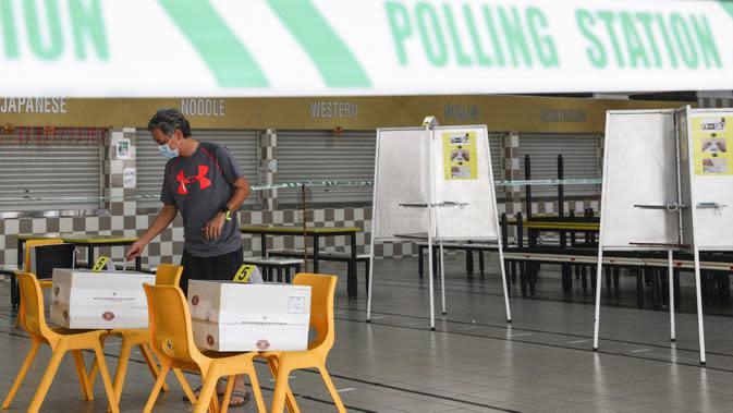 Pemilih memberikan suara dalam pemilu di TPS Sekolah Tinggi Chung Cheng, Singapura, Jumat (10/7/2020). Pemilu di tengah pandemi COVID-19, warga Singapura memberikan suara mereka dengan mengenakan masker dan sarung tangan plastik. (AP Photo)