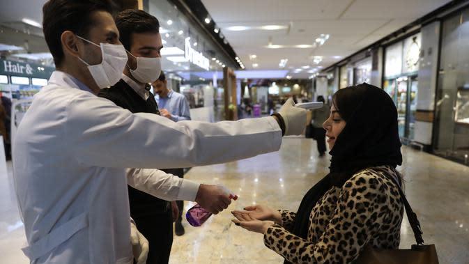 Seorang wanita saat diperiksa suhu tubuhnya dan tangannya ketika memasuki Pusat Perbelanjaan Palladium, di Teheran utara, Iran, Selasa (3/3/2020). Demam yang merupakan salah satu gejala dari infeksi corona menjadikan termometer sebagai salah satu alat untuk mendeteksi. (AP Photo/Vahid Salemi)