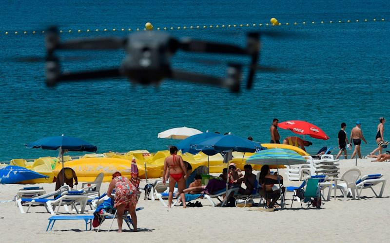 A drone flown by local police warns people to respect social distancing