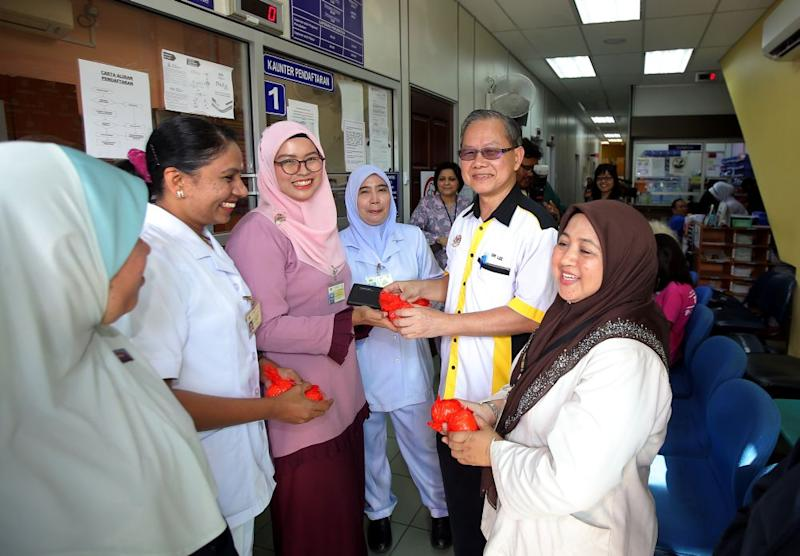 Deputy Health Minister Dr Lee Boon Chye distributes mandarin oranges to staff at the Bijih Timah Health Clinic in Ipoh January 17, 2020. — Picture by Farhan Najib