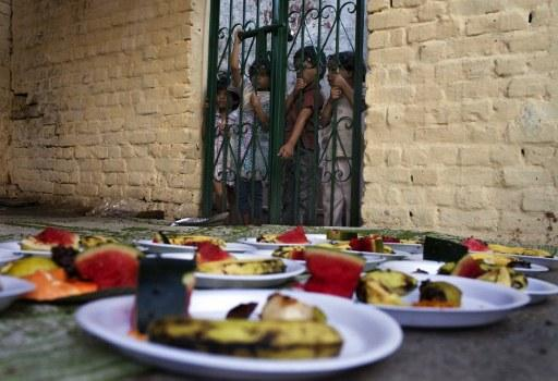 Indian Muslim children look at food being prepared from behind a fence while waiting for food handouts before breaking their fast at sunset during Ramadan at the shrine of 13th century Sufi Muslim saint Hazrat Nizamuddin Aulia in New Delhi on August 12, 2012. Islam's holy month of Ramadan is calculated on the sighting of the new moon and Muslims all over the world are supposed to fast from dawn to dusk during the month.  AFP PHOTO/ Andrew Caballero-Reynolds