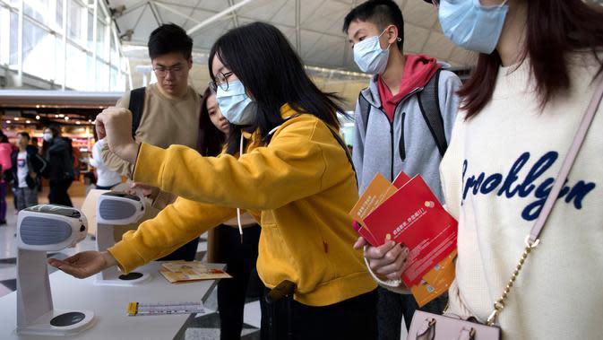 Para pelancong mengenakan masker wajah saat berada di Bandara Internasional Hong Kong di Hong Kong, Selasa (21/1/2020). Masker terjual habis dan pemeriksaan suhu di bandara dan stasiun kereta api menjadi norma baru di China menyusul merebaknya wabah virus corona. (AP/Ng Han Guan)