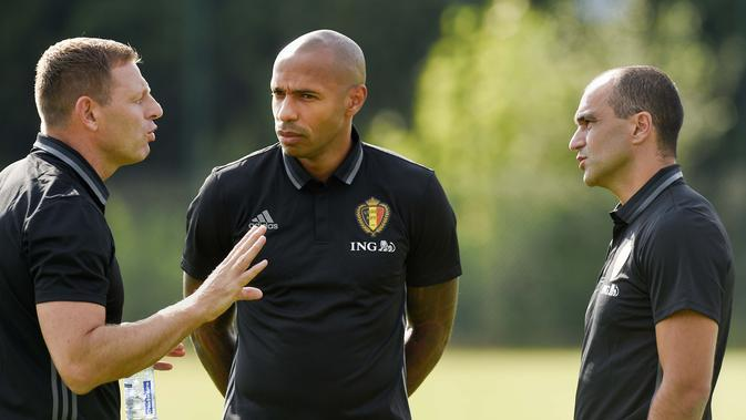 Asisten pelatih Belgia, Thierry Henry (tengah) berbincang dengan asisten pelatih Graeme Jones (kiri) dan Pelatih Kepala Roberto Martinez (kanan) pada sesi latihan sebelum melawan Spanyol di Neerpede, (29/8/2016). (AFP/John Thys)