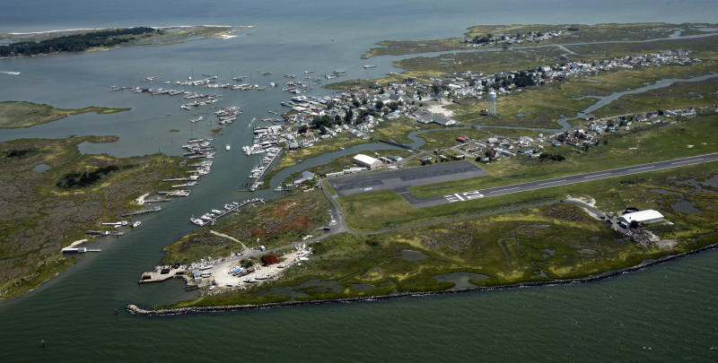 FILE - This Aug. 2, 2011 file photo shows a stone seawall, lower right, on the west side of Tangier Island, Va., which protects the island's airstrip. The fishing community in the middle of the Chesapeake Bay has reported zero cases of the coronavirus. But the virus would be devastating if it were to reach the island, which has a large elderly population and no full-time doctor. (Bob Brown/Richmond Times-Dispatch via AP)