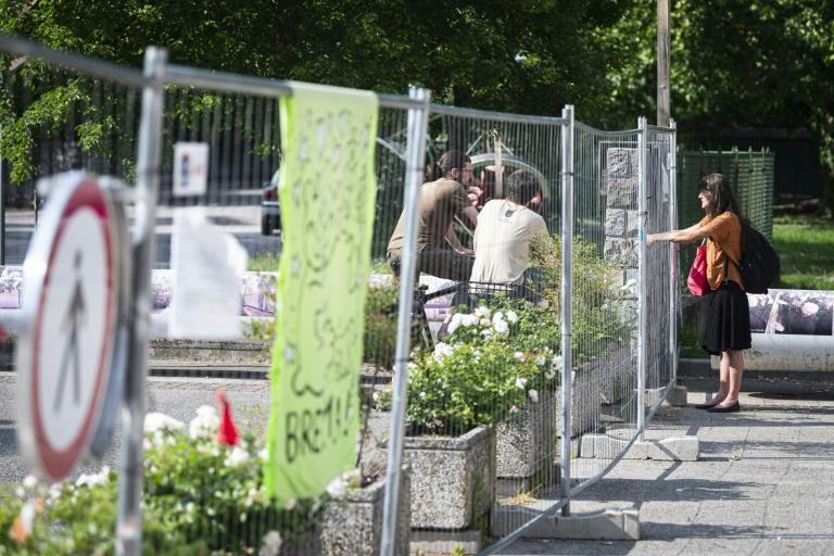 People chat across the border fence between Slovenia and Italy on June 3, 2020. The fence was erected due to the COVID-19 pandemic. Italy is now reopening borders
