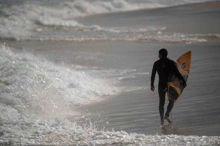 A surfer walks at the Arpoador beach in Rio de Janeiro on June 2, 2020 as some beaches reopened to surfers and swimmers