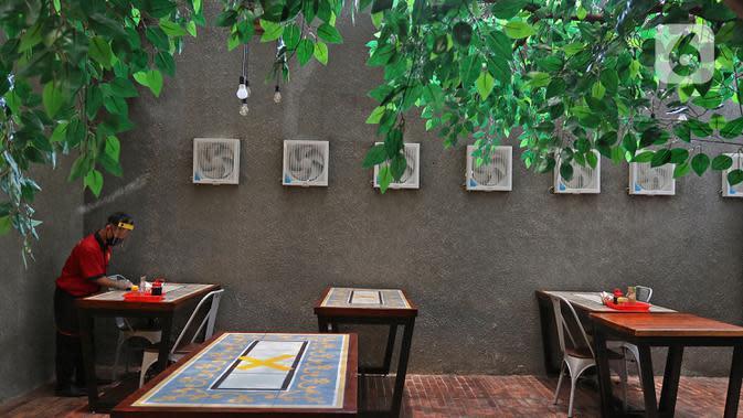 Pramusaji membersihkan meja di restoran Bebek Kaleyo, Kemanggisan, Jakarta, Senin (12/10/2020). Pada penerapan kembali masa PSBB Transisi Jakarta, restoran dan cafe diperbolehkan melakukan pelayanan makan di tempat dengan protokol kesehatan yang ketat. (Liputan6.com/Herman Zakharia)