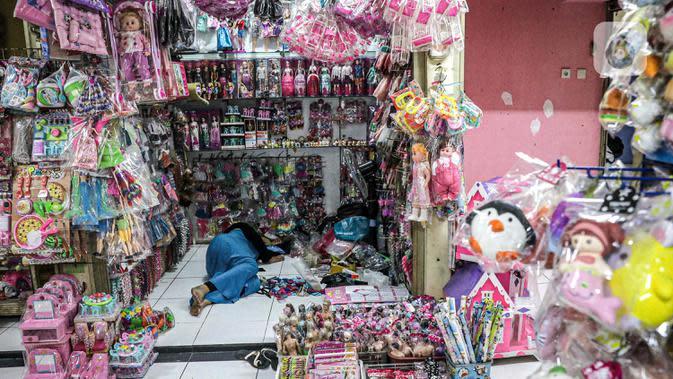 Pedagang tidur di dalam lapaknya di Pasar Gembrong Baru, Cipinang, Jakarta, Jumat (25/9/2020). Para pedagang mengatakan akibat pandemi covid-19 ini omzetnya turun hingga 80 persen, mereka pun berharap masih diperbolehkan berjualan meski PSBB Jakarta kembali diperpanjang. (Liputan6.com/Faizal Fanani)