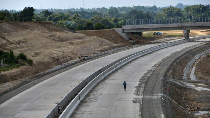 Seorang pria melintas di jalan tol ruas Banda Aceh- Sigli seksi 4 Indrapuri - Blang Bintang di Aceh, Jumat (21/2/2020). Ruas jalan tol Sigli - Banda Aceh sepanjang 74 km itu merupakan tol pertama di Aceh dan bagian dari Jalan Tol Trans Sumatera (JTTS). (Photo by CHAIDEER MAHYUDDIN / AFP)