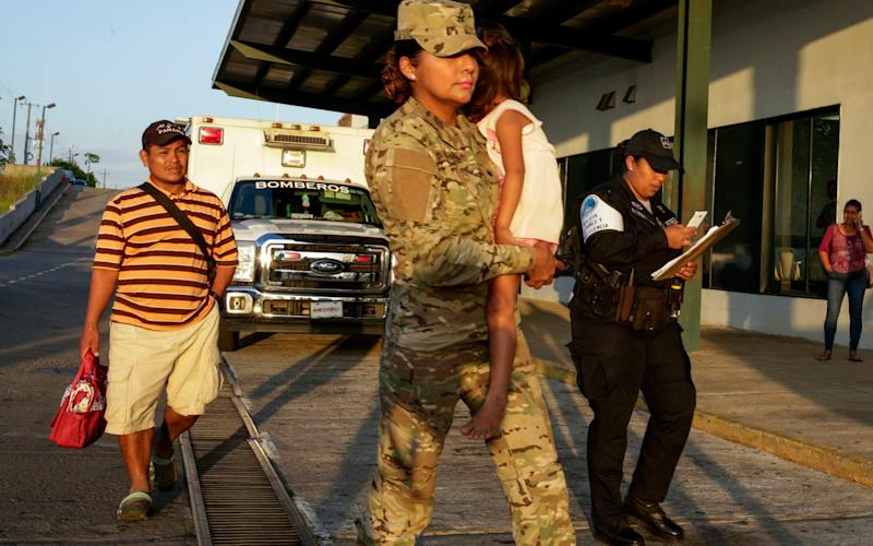 Jose Gonzalez, left, and his daughter, 5, carried by a police officer. Mr Gonzalez's wife and five of their children were killed - AP