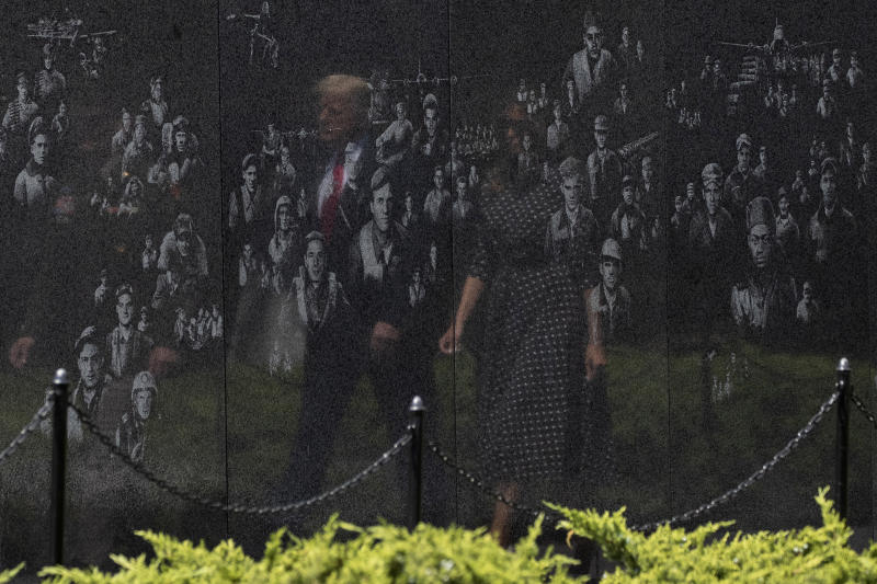 FILE - In this June 25, 2020, file photo reflected in a memorial, President Donald Trump, accompanied by first lady Melania Trump, arrives at the Korean War Veterans Memorial for a wreath placing ceremony in Washington. The relationship between the nation's military community and the Republican president has been strained repeatedly over the course of Trump's turbulent first term. (AP Photo/Alex Brandon, File)
