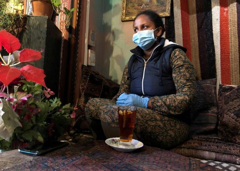 FILE PHOTO: A woman wears a mask and gloves as a measure to combat the spread of coronavirus disease (COVID-19) at a restaurant in Cape Town