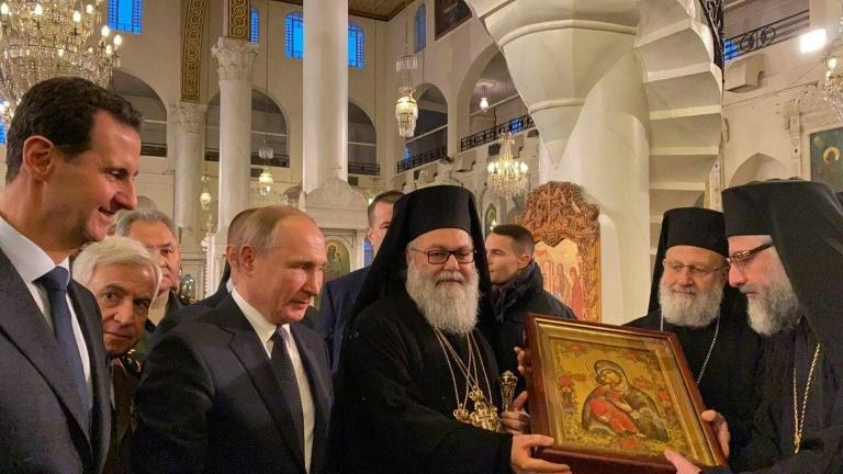 Russian President Vladimir Putin and Syrian President Bashar al-Assad visited the MariamiteCathedral in Damascus 3rd L) the Mariamite Cathedral of Damascus, one of the oldest Greek Orthodox churches in the Syrian capital, near Greek Orthodox Patriarch of Antioch and All East John X Yazigi (C).Putin met his Syrian counterpart Bashar al-Assad during an unprecedented visit to Damascus as the prospect of war between Iran and the United States loomed over the region