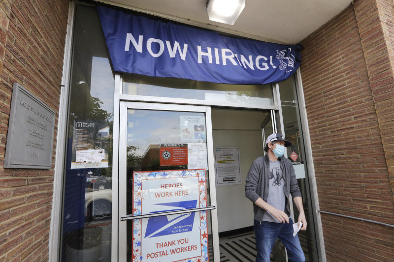 In this photo taken Thursday, June 4, 2020, a customer walks out of a U.S. Post Office branch and under a banner advertising a job opening, in Seattle.  The U.S. unemployment rate fell to 13.3% in May, and 2.5 million jobs were added — a surprisingly positive reading in the midst of a recession that has paralyzed the economy and depressed the job market in the wake of the viral pandemic (AP Photo/Elaine Thompson)