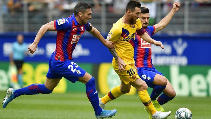 Striker Barcelona, Lionel Messi, berusaha melewati pemain Eibar pada laga La Liga 2019 di Stadion Ipurua, Sabtu (19/10). Barcelona menang 3-0 atas Eibar. (AP/Alvaro Barrientos)