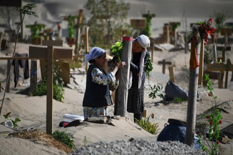 Two women decorate a grave in a Uighur cemetery on the outskirts of Hotan in China's northwest Xinjiang region in May 2019
