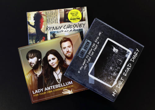 This Oct. 30, 2013 photo shows CDs of Luke Bryan, Lady Antebellum and Kenny Chesney that were produced to influence voters of the CMA Awards in Nashville, Tenn. The CMA encourages artists and their labels to educate voters, allowing three email blasts and one mailed product a year. (AP Photo/Mark Humphrey)