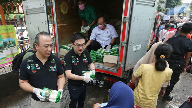 Direktur Sugar Group Companies Yusuf Sumartha dan Irwan Ang memberikan gula pasir kepada warga saat Operasi Pasar di Pasar Palmerah, Jakarta, Jumat (20/3/2020). Sugar Group Companies menjamin ketersediaan gula selama satu di 35 titik pasar wilayah DKI Jakarta dan Banten. (Liputan6.com/Fery Pradolo)