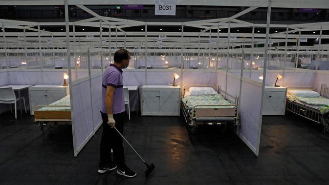 Seorang pekerja membersihkan rumah sakit lapangan sementara yang didirikan di Asia World Expo di Hong Kong, Sabtu (1/8/2020). Pusat pameran di dekat Bandara Internasional Hong Kong itu diubah menjadi fasilitas untuk menampung pasien COVID-19 dengan gejala ringan. (AP Photo/Kin Cheung)