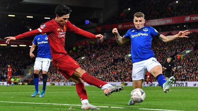 Gelandang Liverpool, Takumi Minamino berusaha mengumpan bola dari kawalan pemain Everton, Lucas Digne pada pertandingan babak ketiga Piala FA di Anfield, Minggu (5/1/2020). Selama di lapangan, Minamino melakukan 33 kali sentuhan. (AFP/Paul Ellis)
