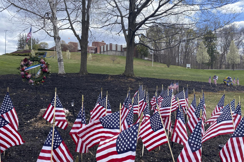 Flags and wreaths honor veterans, Tuesday, April 28, 2020, on the grounds of the Soldiers' Home in Holyoke, Mass., where a number of people died due to the coronavirus. While the death toll at the state-run Holyoke Soldiers' Home continues to climb, federal officials are investigating whether residents were denied proper medical care while the state's top prosecutor is deciding whether to bring legal action. (AP Photo/Rodrique Ngowi)