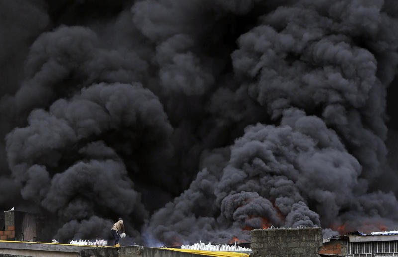 A man with a bucket tackles a blaze as smoke rises from a fire in downtown Lagos, Nigeria, Tuesday, Nov. 5, 2019. (Photo: Sunday Alamba/AP)