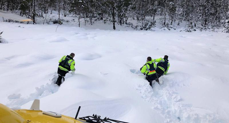 Photo of three officers battling their way through waist-deep snow in Tasmania.