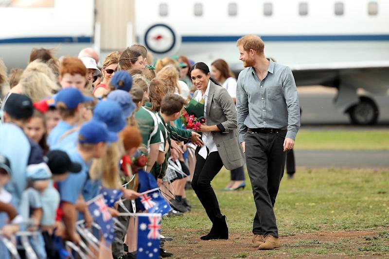 Local school children line up catch a glimpse of the royal couple. Photo: Getty, meghan markle prince harry dubbo, meghan markle prince harry australia, meghan markle serena williams jacket, meghan markle pregnant