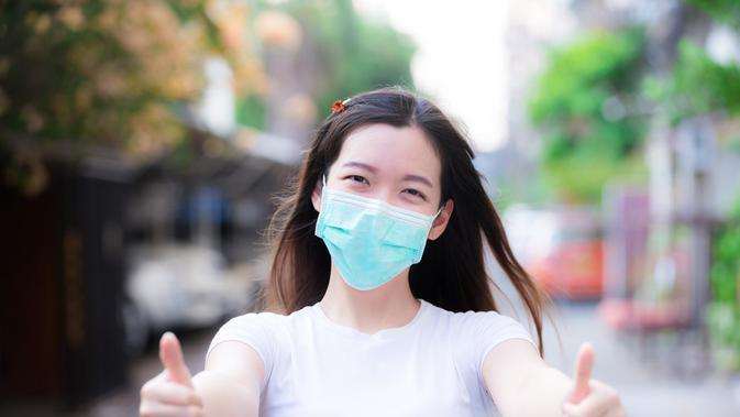 Seorang wanita tersenyum di balik masker. ©Shutterstock