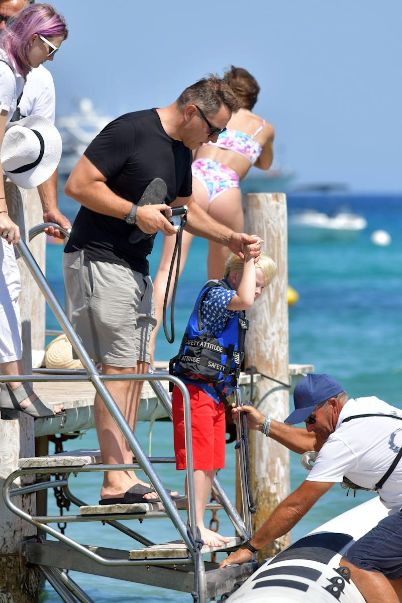 David Walliams dressed in dark clothes helps small blond child in life vest onto a speed boat in Saint-Tropez