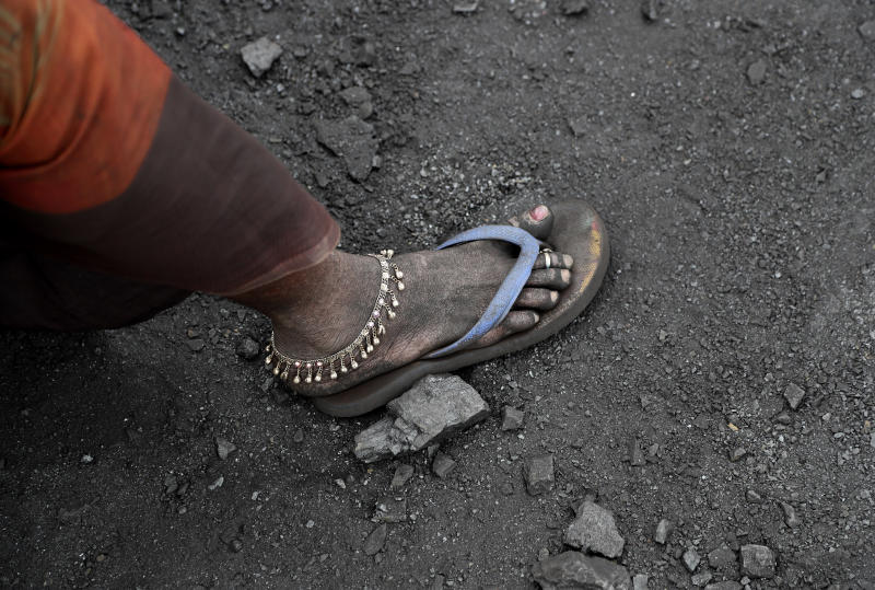 In this Oct. 23, 2019, photo, a laborer sports an anklet as she takes a break from loading coal into trucks for transportation in the village of Godhar in Jharia, a remote corner of eastern Jharkhand state, India. The fires started in coal pits in eastern India in 1916. More than a century later, they are still spewing flames and clouds of poisonous fumes into the air, forcing residents to brave sizzling temperatures, deadly sinkholes and toxic gases. (AP Photo/Aijaz Rahi)