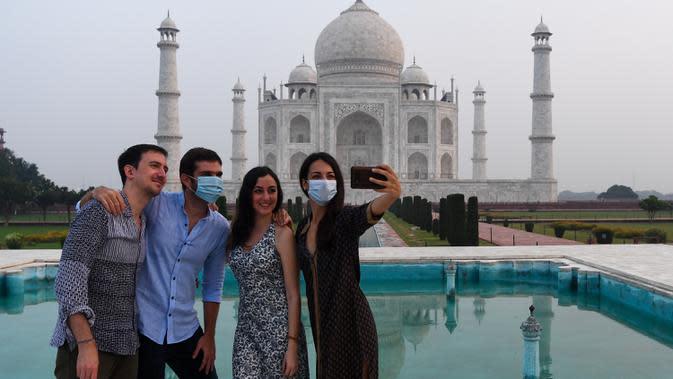 Turis berfoto dengan latar belakang Taj Mahal di Agra, India pada Senin (21/9/2020). Taj Mahal kembali dibuka untuk umum hari ini, Senin (21/9), saat negara dengan 1,3 miliar orang itu telah mencatat lebih dari 5,4 juta kasus Covid-19. (Sajjad HUSSAIN/AFP)
